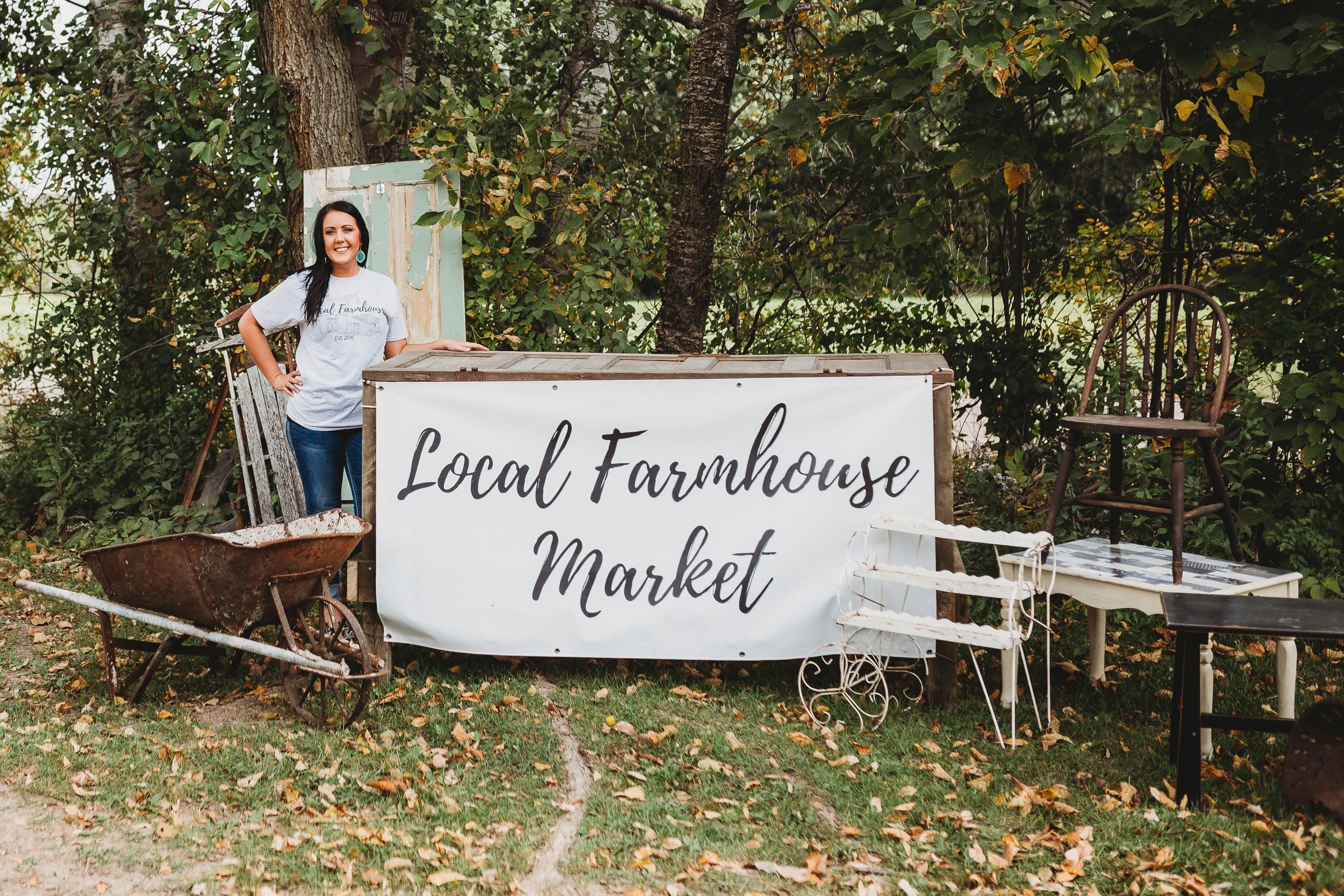 "Young woman with ""Local Farmhouse,"" sign."