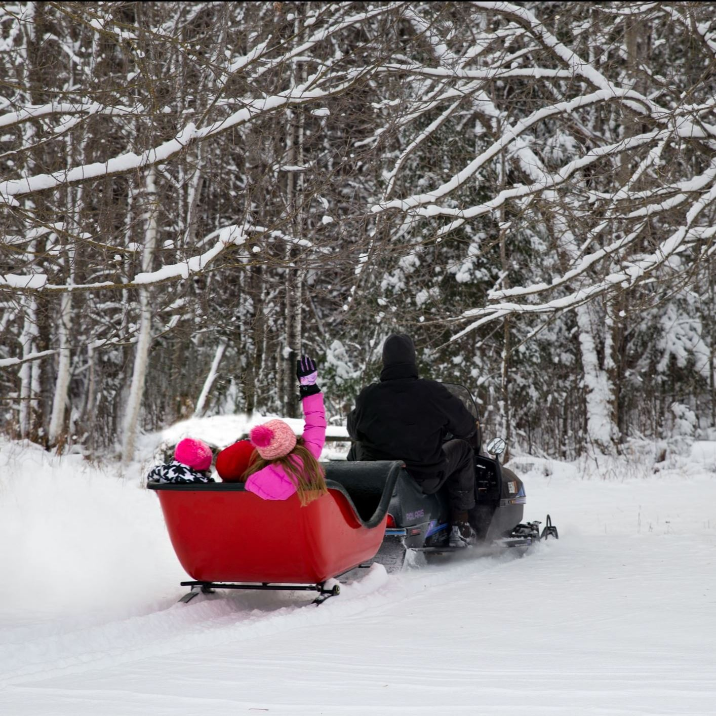 Snowmobile pulling small sled with children.