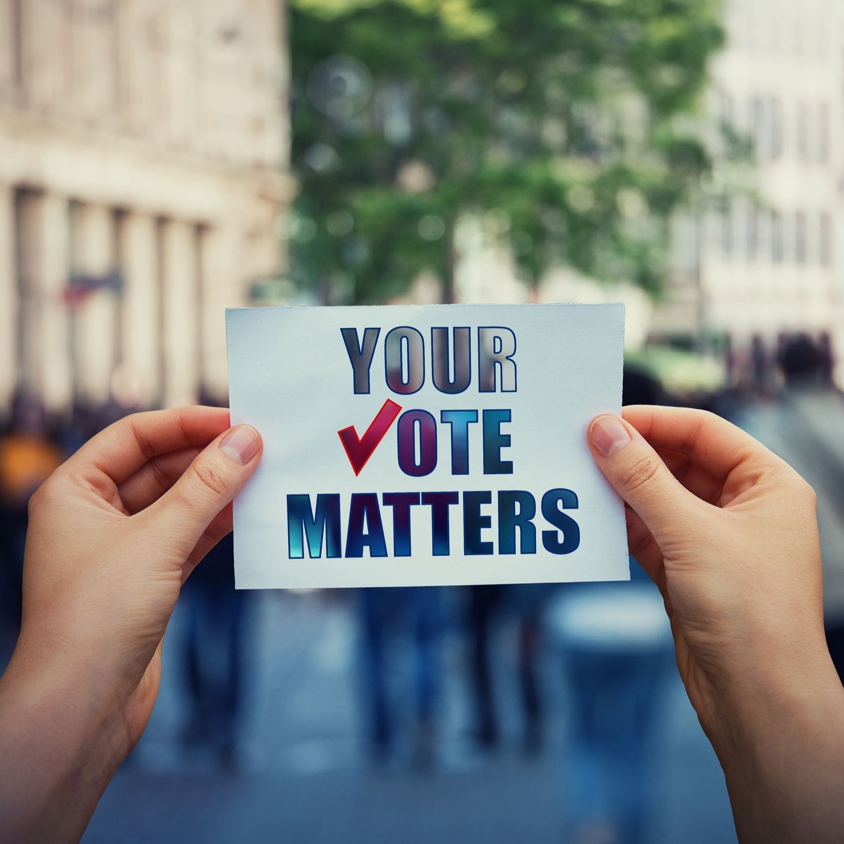 "Person holding ""Your Vote Matters,"" sign"