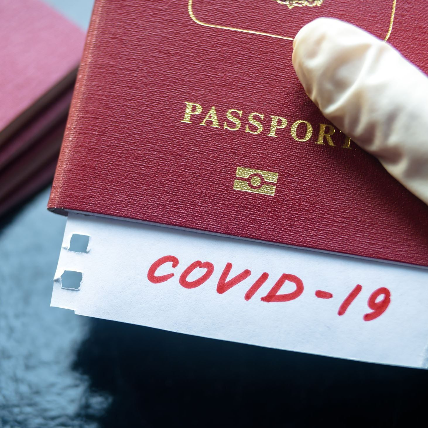 """COVID-19"" note sticking out of passport."