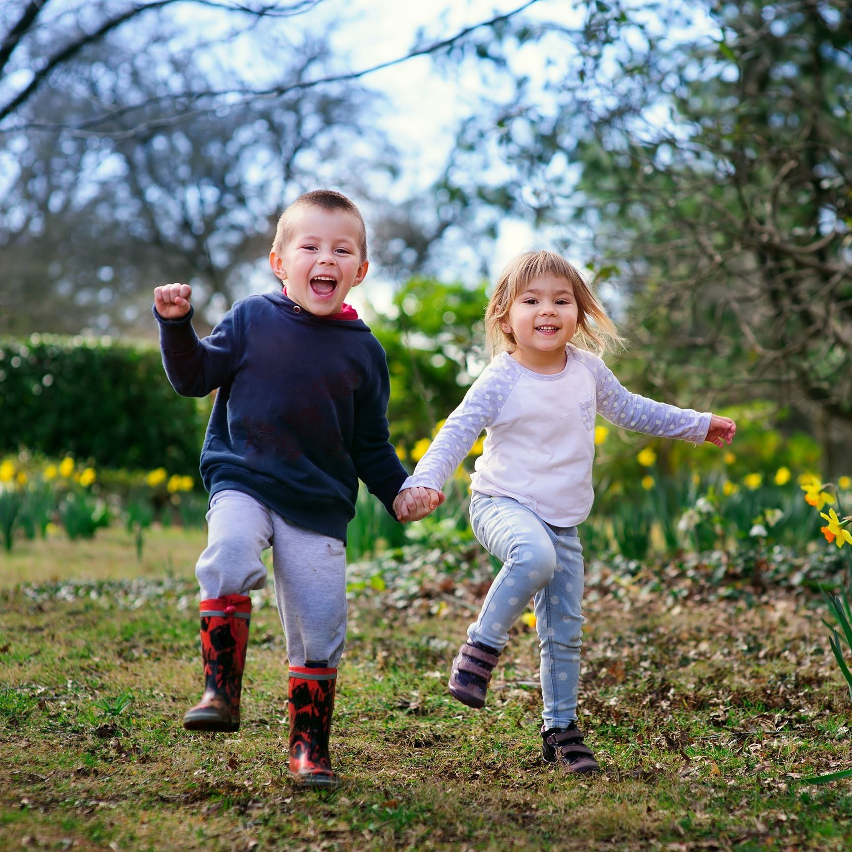 Happy children running through grass.