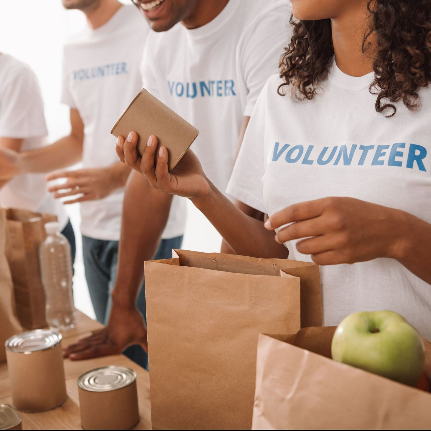 People volunteering to fill bags at a food shelf.