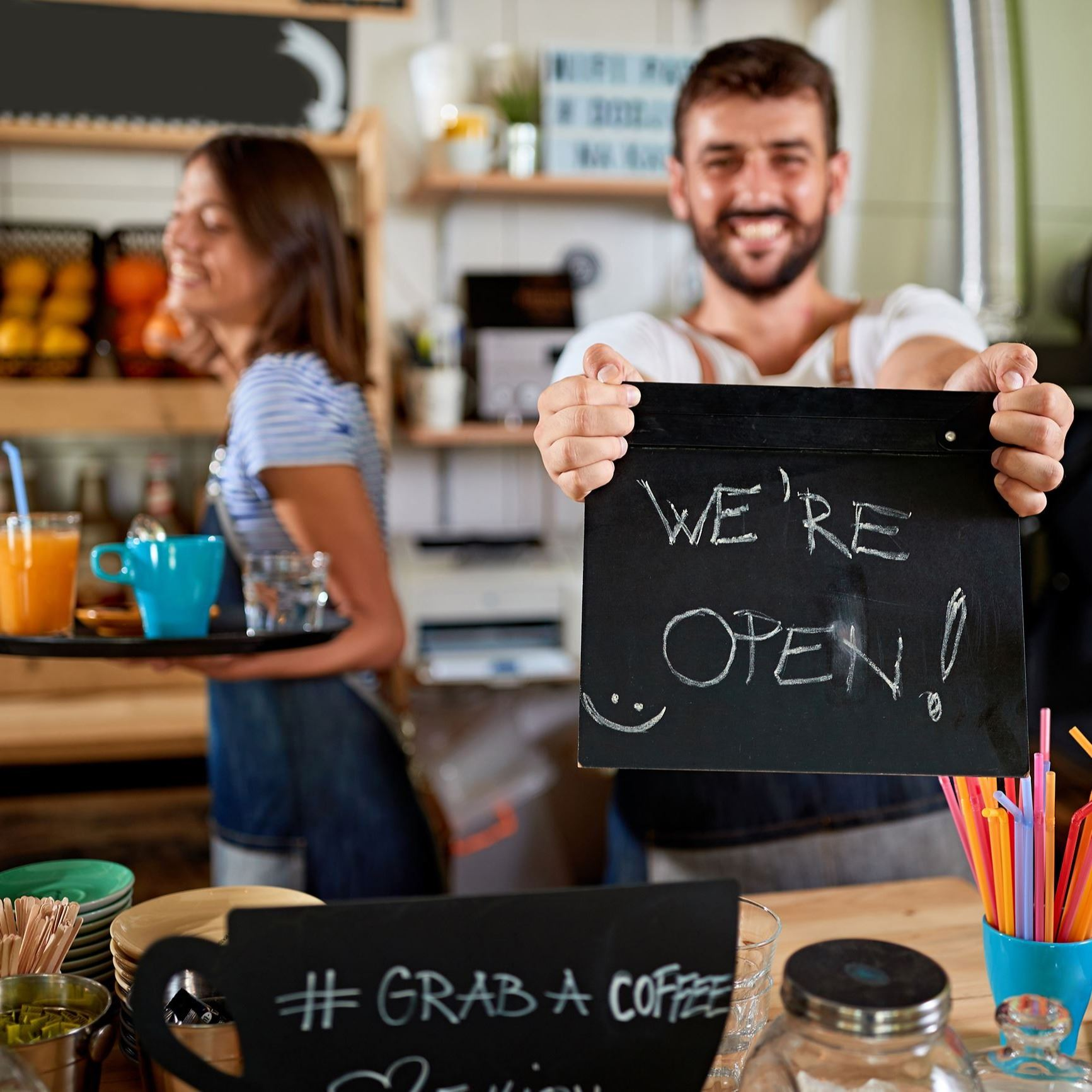 "Male barista holding a ""we're open!"" sign."