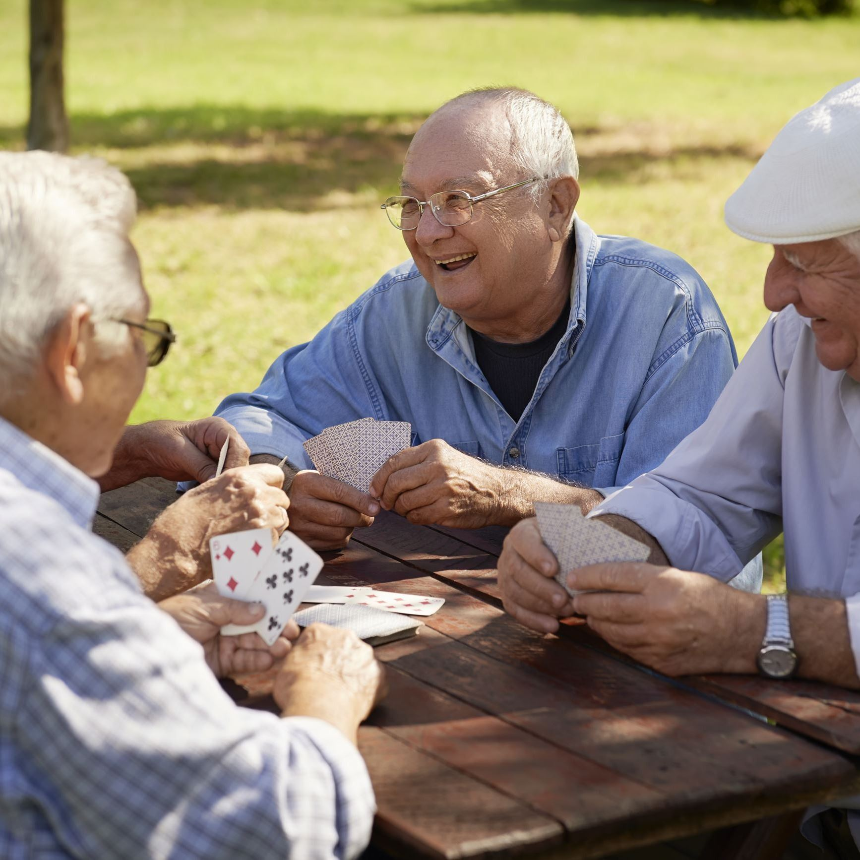 Elderly people in park playing cards.