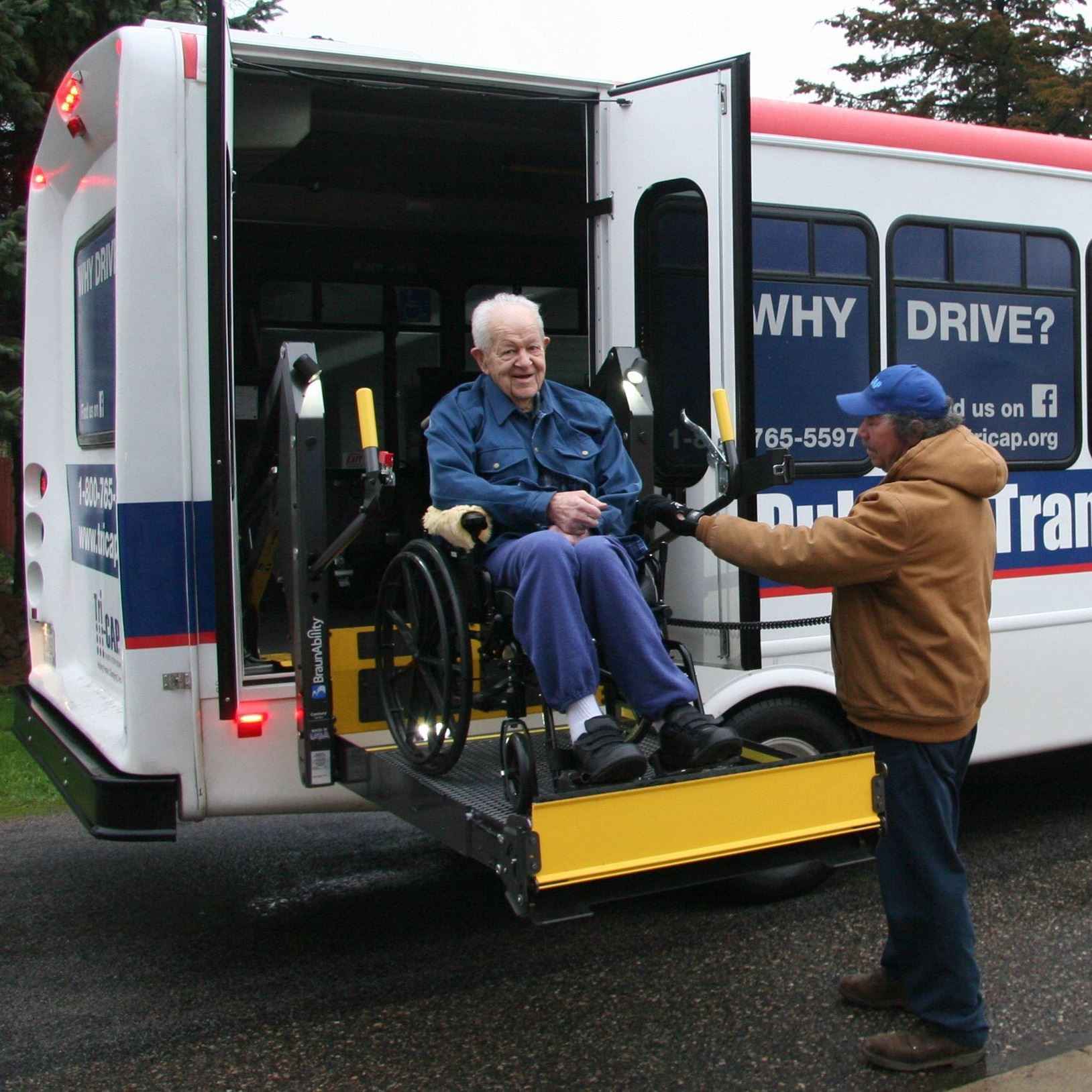 Man in wheelchair getting on Tri-CAP bus.