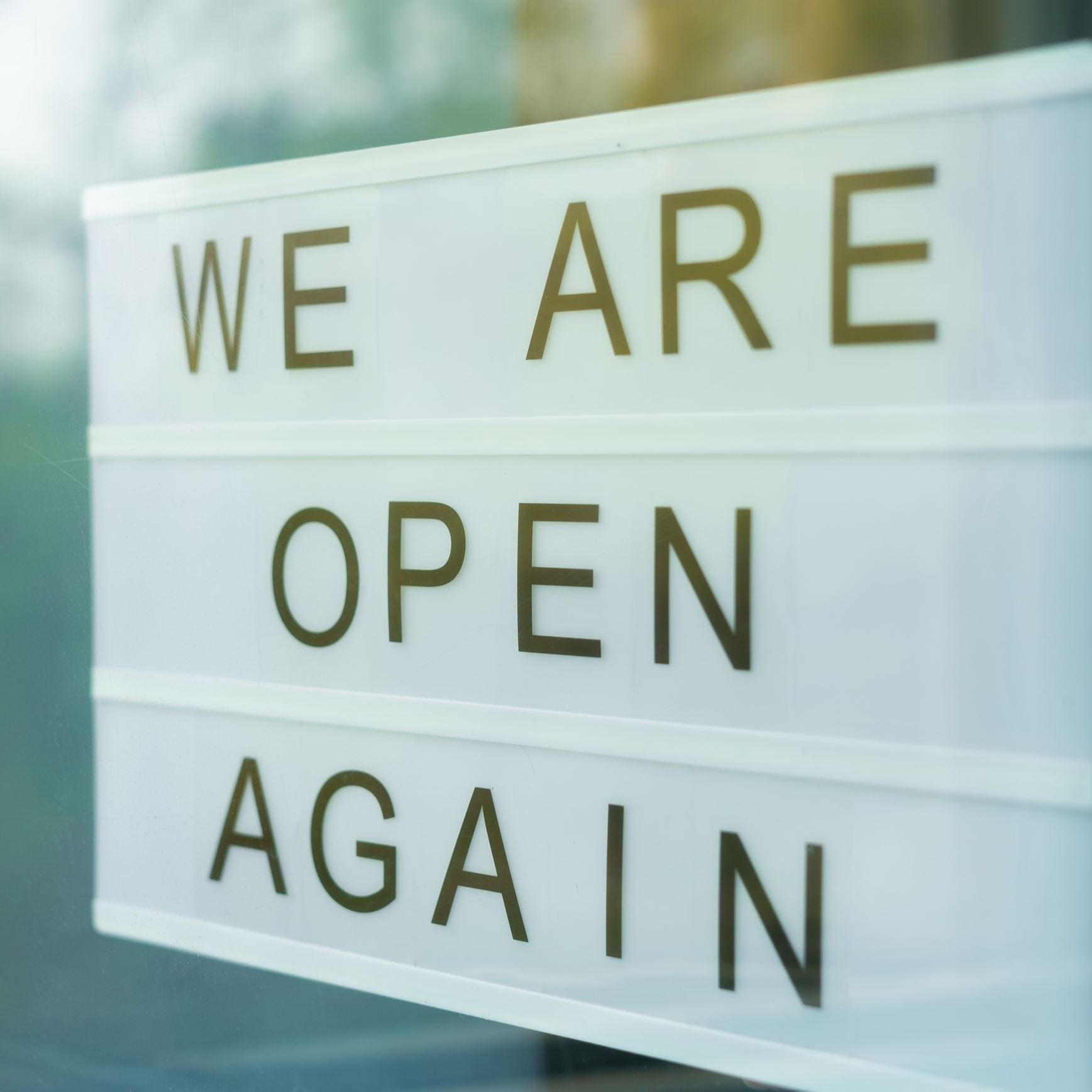 """We are open again"" sign hanging in window."