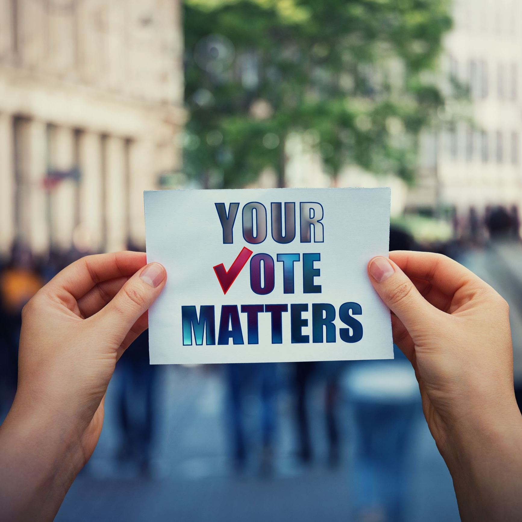 "Person holding up a paper that says, ""Your vote matters."""