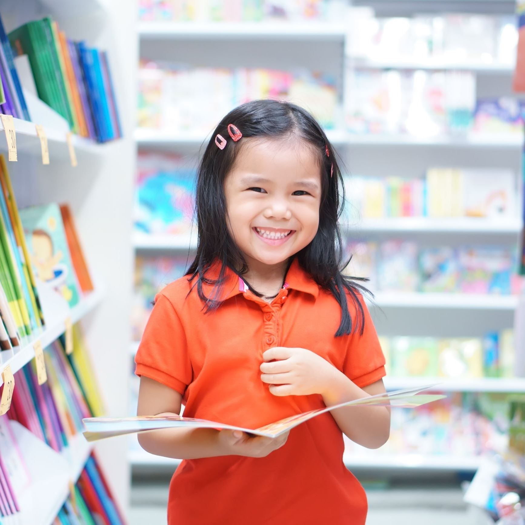 Young smiling girl in library with book.