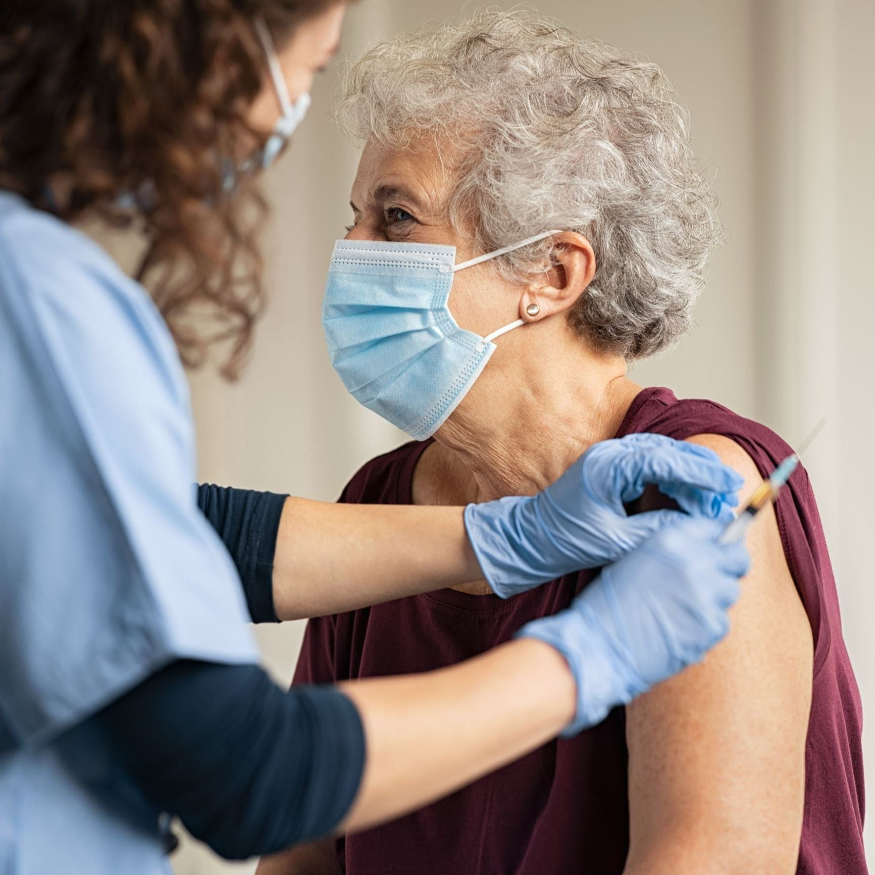 Elderly woman receiving a COVID-19 vaccine from a nurse.