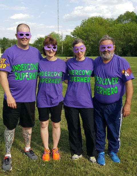 Smiling Group Wearing Masks and Purple Shirts that Say